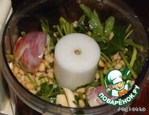 В комбайн уложить зелень петрушки (предварительно ополоснуть её в холодной воде), чеснок, лук, кедровые орешки. Добавить половину растительного масла.