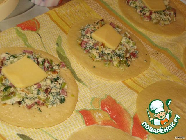Духовку разогреть до 180 С.   Теперь из двух блинчиков будем делать лепешки.    На одну лепешку выложить часть порезанного омлета, в середину положить по кусочку сыра.    Края (по 0,5 см), каждой лепешки, пальчиком смазать молоком или кефиром, для большей сцепки )))