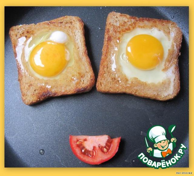 В отверстия в хлебе влить яйца. Огонь убавить, накрыть крышкой.