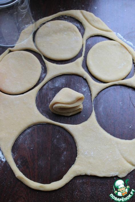 При необходимости добавить немного муки и раскатать тесто в не очень тонкий пласт. Стаканом (у меня диаметр 7,5 см.) вырезать кружочки. Каждый свернуть в конвертик (пополам, а потом ещё раз пополам).
