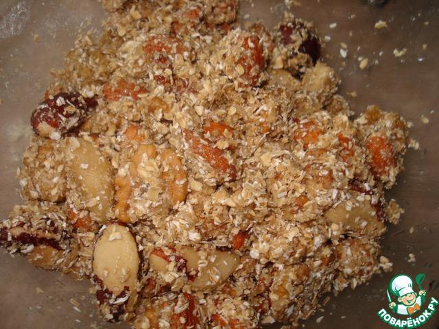 Засыпьте овсяную смесь в миску и очень аккуратно перемешайте вместе с орехами.