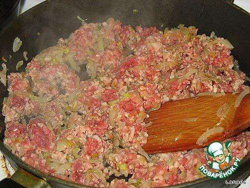 На разогретой с маслом сковороде обжарить лук до золотистого цвета. Добавить фарш и интенсивно перемешать.