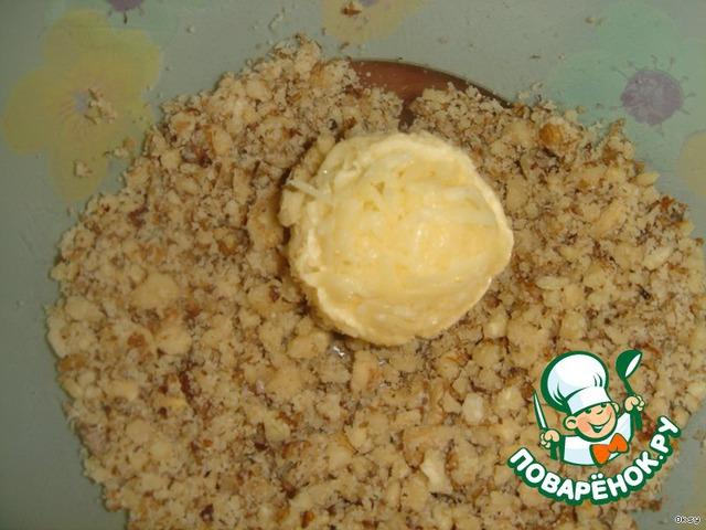 Из сырной массы скатать шарики величиной с маленький грецкий орешек, спрятав в каждый шарик по оливке. Затем плотно скатанные шарики обвалять в орехах.