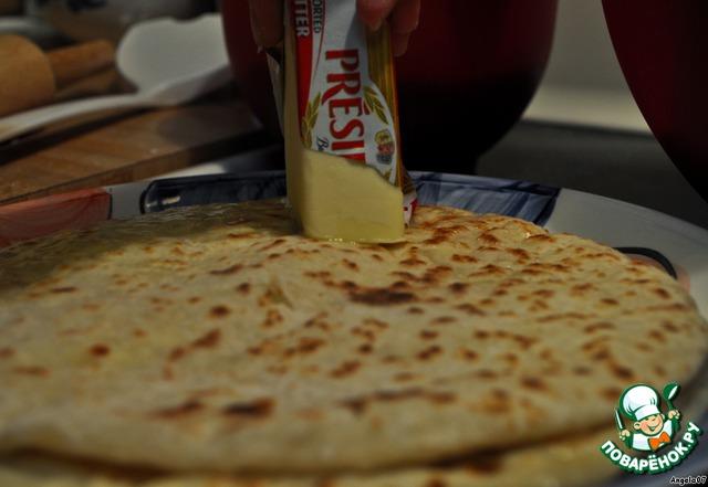 Снимите хичин со сковороды и сразу обильно помажьте сливочным маслом. Уделите особое внимание краям.