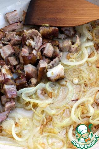 Разогреть в сковороде растительное масло и обжарить лук,    после добавить кусочки копченого мяса, прогреть пару минут.