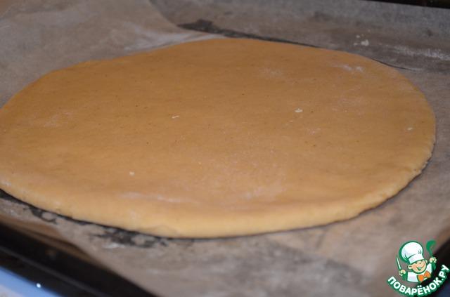 Раскатать одну половинку не тонко, примерно 0,5-0,6 см, у меня в форме круга и переложить ее на противень.