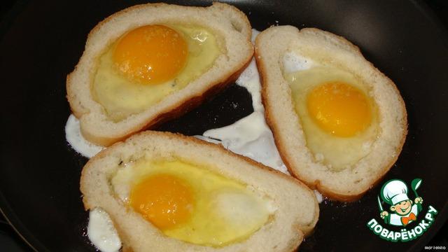 Через полминутки в каждый ломтик вбиваем по яйцу. Подсаливаем.