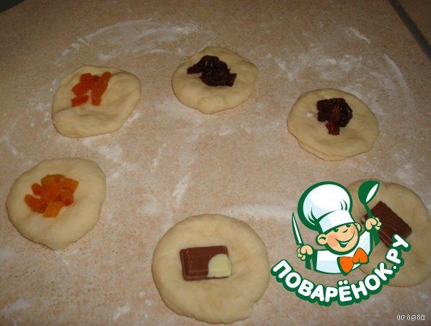Тесто, после того как подросло, еще раз помнем. И отставим на 15 минут.    После того, как тесто постоит, мы берем и отрываем кусочки, одинаковые по размеру. Каждый кусочек разминаем в лепешку и кладём на нее начинку.