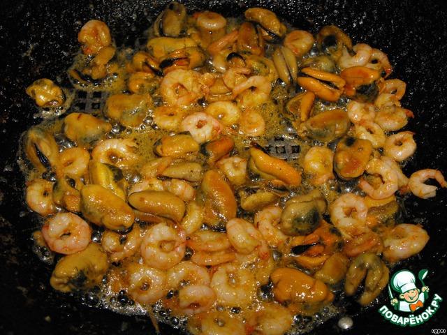 На сковороде нагреть оливковое масло, подрумянить 2 дольки чеснока (предварительно чеснок раздавить).   Чеснок вынуть и добавить подготовленные мидии и креветки