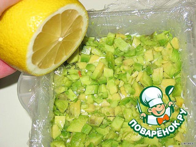 Третий слой - авокадо. Разрезать пополам, мякоть нарезать на кубики. Сбрызнуть соком лимона и смазать майонезом.