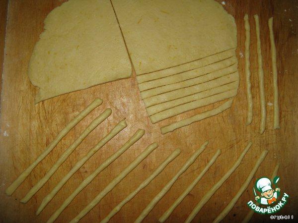 Раскатайте тесто в пласт, толщиной 0,5 см, нарежьте его на полосочки и каждую полосочку скатайте пальчиками в трубочку.
