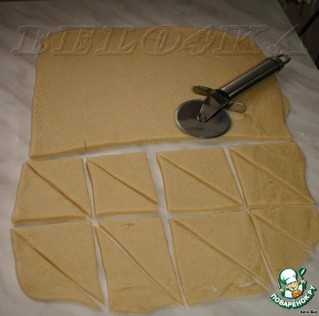 Раскатать опять до 5 мм толщиной, опять посыпать столовой ложкой сахара, опять сложить. И так ещё 4 раза.    Посыпая - складывая - раскатывая, мы создаем слоистость теста.    Итак, перед нами в конечном итоге оказывается пласт толщиной 5 мм. Его мы нарезаем треугольниками.    Форма не принципиальна, можно вырезать формочками для печенья, можно квадратиками, кружочками... В общем, как вам нравится.