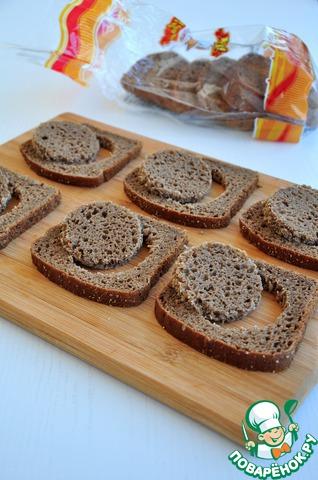 Из бородинского хлеба вырезать рюмкой кружки для селедочных рулетов.