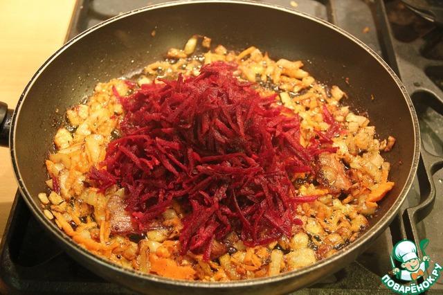 Морковь жарим 2-3 минуты и добавляем буряк, тёртый на крупной тёрке. Держим ещё на сковороде около 5-7 минут.
