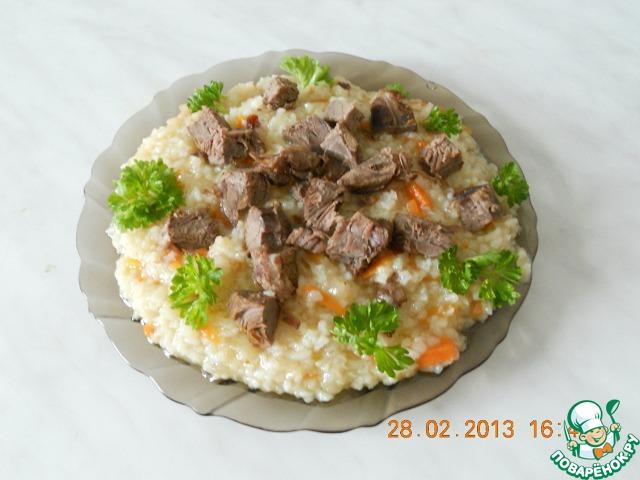 Мясо нарезать мелкими кусочками. Готовый плов выложить на большое блюдо, сверху горкой выложить нарезанное мясо, украсить зеленью.
