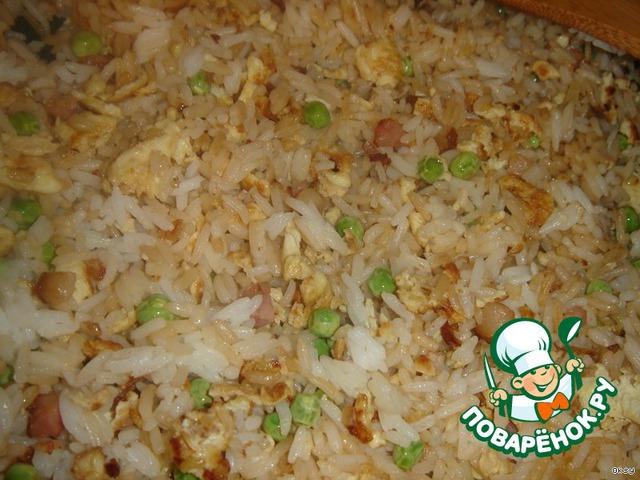 Добавить отваренный рис и все вместе перемешать в сковороде. Жарить все вместе несколько минут, пока рис не прогреется. В конце добавить поджаренный ранее бекон, полить соевым соусом, приправить по вкусу солью и перцем.