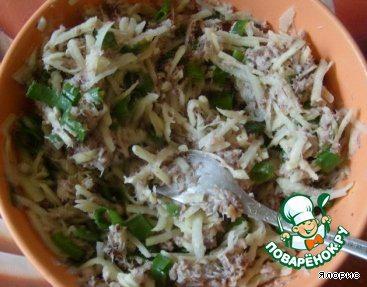 Разминаем вилкой рыбные консервы, перемешиваем с мелко нарезанным зеленым луком и крупно натертым сырым картофелем, солим.