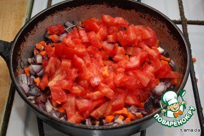 Туда же отправляем нарезанный кубиками помидор, перемешиваем и тушим минут 10 под крышкой на медленном огне.