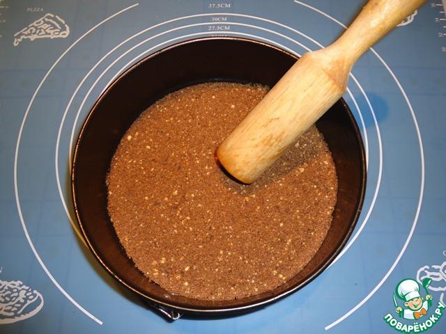 Выкладываем получившуюся шоколадную крошку в форму, с помощью толкушки выравниваем и придавливаем поверхность.
