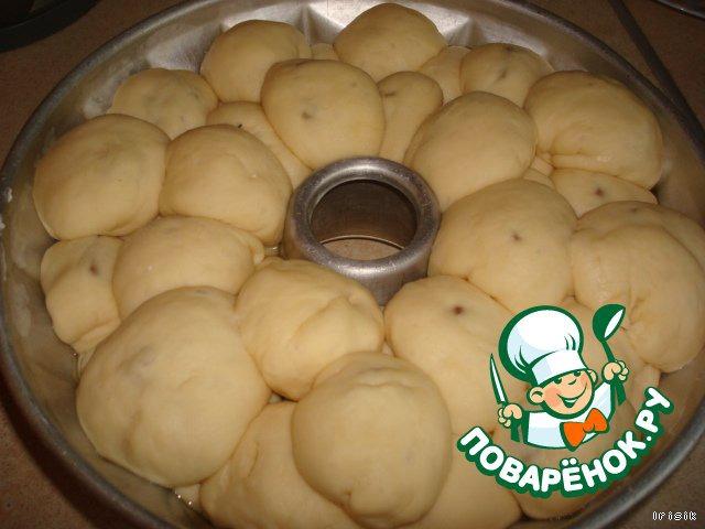 Форму для бабки смазываем подсолнечным маслом и посыпаем сухарями или мукой. Каждый шарик складываем в форму в произвольном порядке. Верх бабки смазываем молоком.   Оставляем, подрасти в форме, на 20 минут.