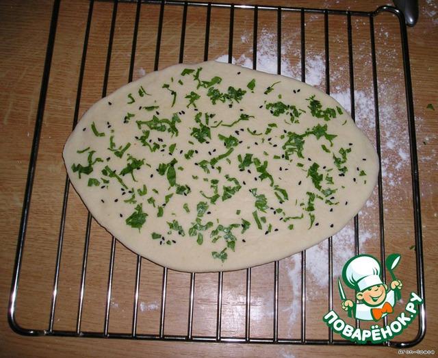 Разделите тесто на 6 равных кусков и раскатайте каждый кусок в овал, толщиной примерно в пол-сантиметра. При желании, каждую лепёшку можете посыпать зеленью и/или какими-нибудь зёрнышками. Я посыпал зеленью петрушки и чёрным кумином (зирой).