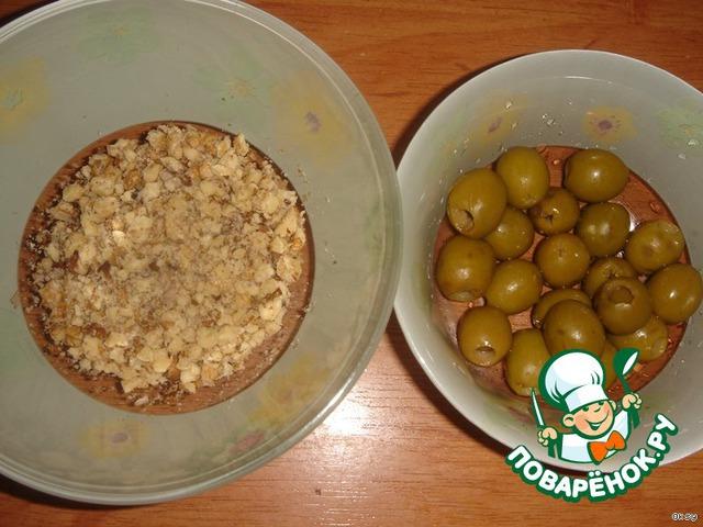 Подготовить оливки и орехи. Орехи я измельчила самым простым способом, чтобы меньше испачкать посуды. Просто сложила в пакет, завязала его и отбила орехи молоточком для мяса.