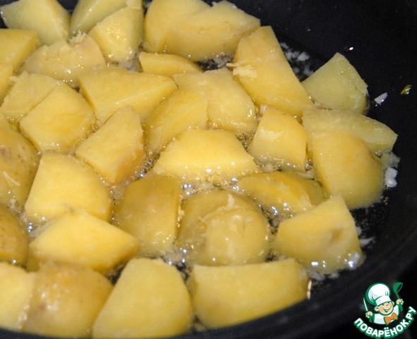 Картофель отвариваем в мундире до полуготовности. Затем, когда он немного остынет, очищаем его и нарезаем крупными ломтиками.   На сковороду наливаем масло, чеснок мелко режем и добавляем к маслу.     Ломтики картофеля обжариваем на сильно разогретом масле до красивой золотистой корочки.