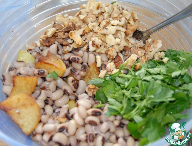 Орехи мелко рубим. Петрушку моем и нарезаем. К картофелю выкладываем фасоль в соусе. Добавляем порубленные орехи и петрушку. Все хорошо перемешиваем.