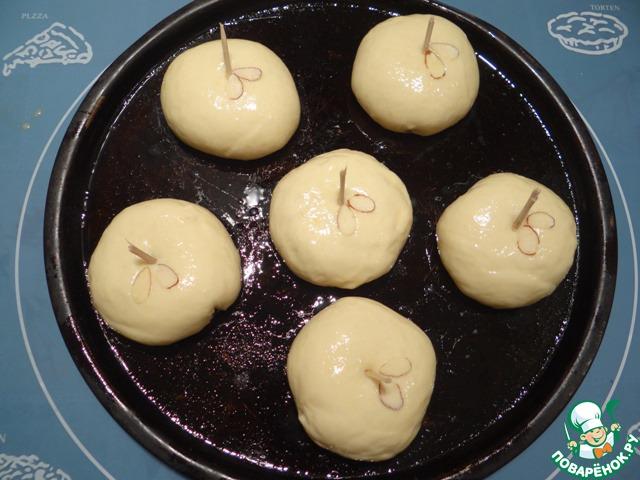 Затем ломаем деревянный шампур, втыкаем в серединку каждого пирожка. Смазываем пирожки взбитым яйцом, у шампура украшаем каждый пирожок миндальными лепестками - это будут листочки у яблочек.