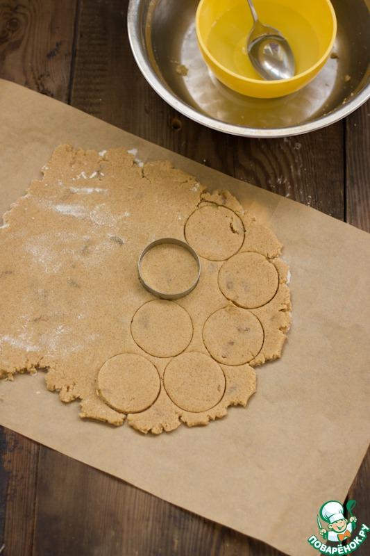 Стол припорошить мукой. Раскатать тесто в пласт толщиной 7-8 мм. При помощи круглой выемки или стакана придать печенью форму.