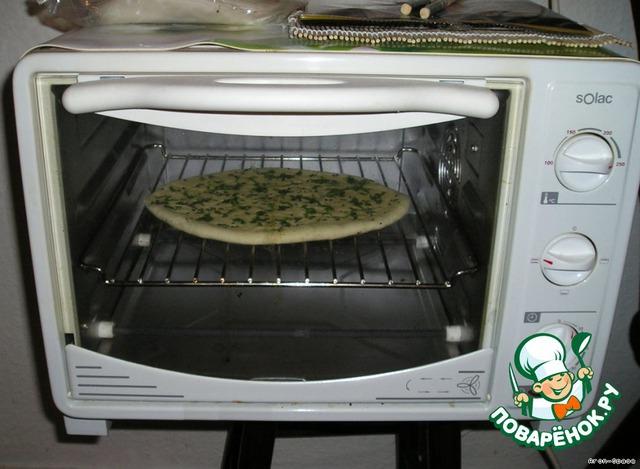 Поставьте это чудо в предварительно разогретую духовку на 5-10 минут. Лепёшка должна начать раздуваться и увеличиваться в объёме. Выпекать нужно при температуре 225 градусов до золотисто-коричневых пятнышек.
