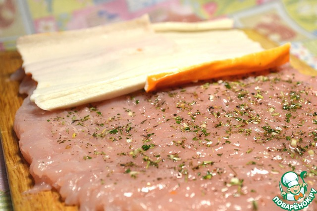 На внутреннюю часть (где нет пленочки) нанести немного маринада, развернуть крабовые палочки, выложить внахлест по всей ширине пласта филе