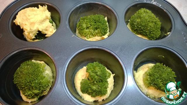 Брокколи достать из воды и высушить на бумажном полотенце.    Подобрать нужный размер соцветий. Поместить каждое соцветие на тесто и углубить, немного вдавливая.     Сверху выложить тесто по 1 столовой ложке на каждое соцветие брокколи. Тесто тягучее, поэтому немного смочите ложку водой и сформируйте, чтобы прикрыть брокколи.
