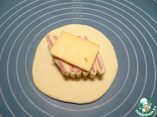 Сверху на кусочки теста с ветчиной кладу кусочек сыра.