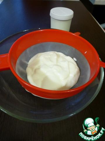 Дуршлаг с очень мелкой сеточкой подвесить на миску, выложить йогурт. Либо завернуть йогурт в марлю, сложенную в несколько слоев, подвесить над миской. Поставить в холодильник на 2-3 часа, для того, чтобы из него стекла вся сыворотка. Эта процедура необходима для любого йогурта, будь он домашний или магазинный.
