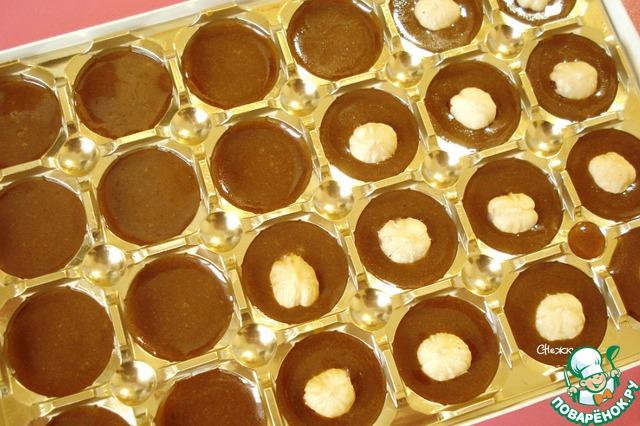 Форму смазываем растительным маслом и заполняем расплавленным ирисом. В каждую ячейку кладём орех...