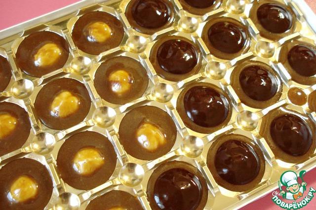 Через 10 минут достаём наши конфеты. Полученную шоколадную массу очень аккуратно, чайной ложечкой, выкладываем на конфеты (как на фото).