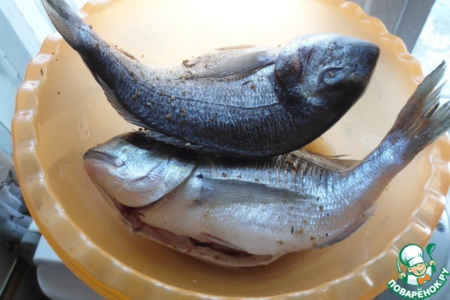 1. Почистим и замаринуем рыбу в лимонном соке. Промаслим дорадо с обеих сторон.