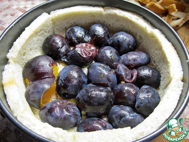 Форму смазываем маслом, выкладываем сливы и заливаем творожной смесью, сверху выкладываем еще слой слив, смазываем сметаной.
