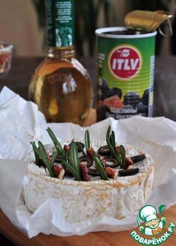 Все очень и очень просто, но очень вкусно.    Камамбер распаковать, снять пленку, пергамент оставить. Также оставить сыр в деревянной коробочке, это необходимо для того, чтобы сыр держал форму при запекании.     Надрезать верх сыра в нескольких местах ножом. Воткнуть в каждый надрез орех, несколько иголок розмарина, нарезанные кружочком маслины.     Мед нужно использовать жидкий, но если мед густой, поставить его на 20-30 секунд в СВЧ.