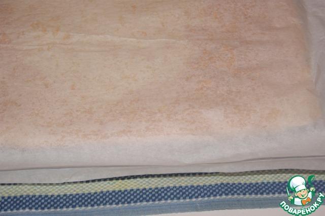 Поместить бисквит вместе с бумагой на полотенце, накрыть чистой бумагой сверху.