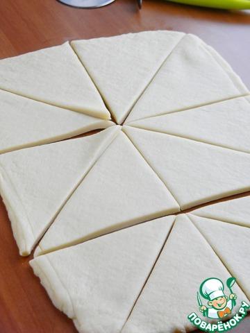 Достать тесто из холодильника, раскатать в прямоугольный пласт, толщина примерно 0,5 см. Разрезать на две полосы, затем на квадраты и каждый квадрат на треугольники. Или лучше сразу полосу нарезать на треугольники.