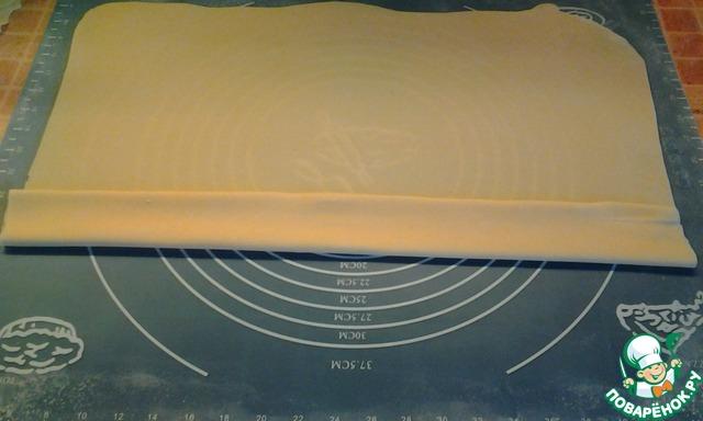 Сворачиваем плоский рулет шириной 4-5 см. Чем больше слоев, тем пышнее пахлава. Край смажьте водой и заклейте, чтобы во время жарки пахлава не развернулась.