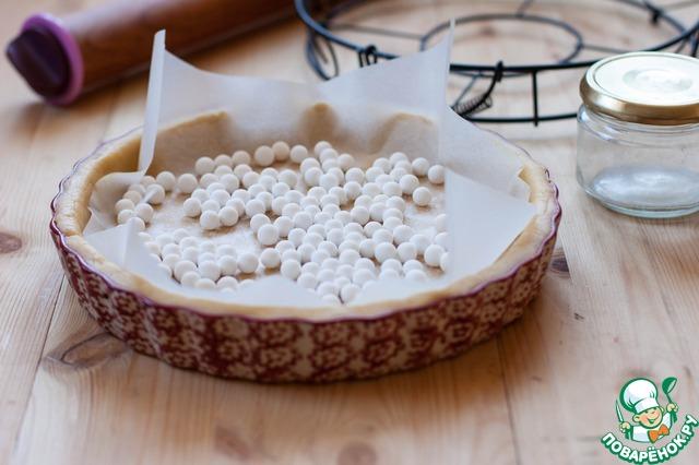 Разогрейте духовку до 180 градусов, на дно формы положите пергамент и заполните его грузом. Поставьте в духовку на 15 минут, затем груз и бумагу уберите и выпекайте основу до равномерного золотистого цвета.