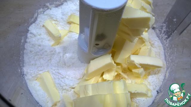 В кухонном комбайне смешайте муку, соль и сливочное масло. Добавьте ледяную воду. Скатайте тесто в шар и поместите в холодильник на 30 минут