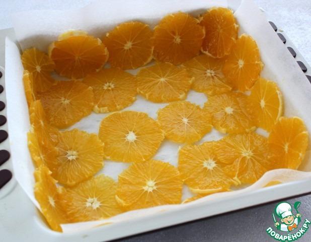Прямоугольную форму выложить промасленной бумагой, по дну и стенкам положить кружочки апельсинов.