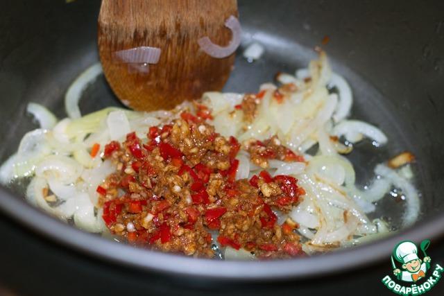 Растолочь в миске чеснок, сладкую паприку, соль, очищенный от семян и мелконарезанный перец чили.   Добавить массу к луку и жарить, помешивая, еще 2 минуты.
