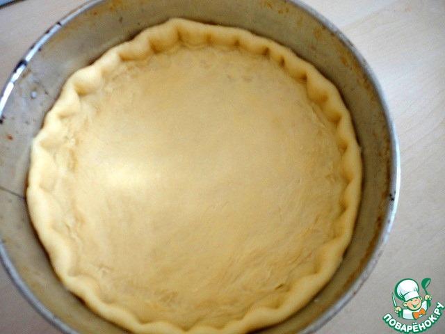 Расскатать тесто и выложить в круглую разъёмную форму ( Ф 26 см ), делая руками бортики и наколоть дно вилкой.