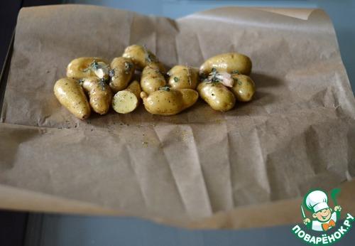 Подготовить большой лист пергамента, визуально поделить его пополам. Выложить картофель на одну половину. Сверху выложить веточки тимьяна и/или розмарина.