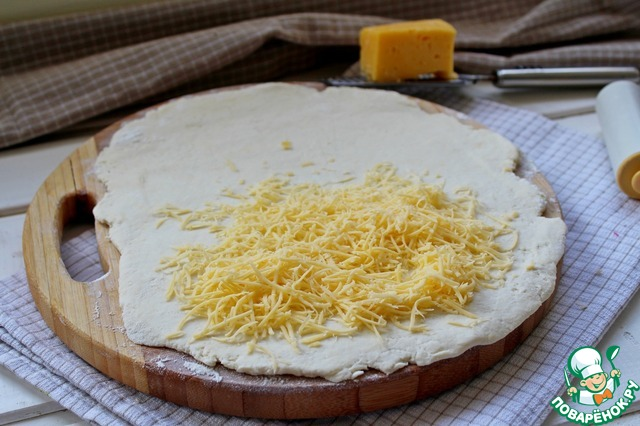 На половину раскатанного пласта выложить натертый сыр.